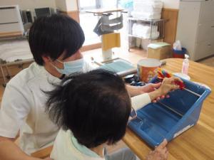 セラピストが患者の手を持ちブロックを移動させるリハビリの様子