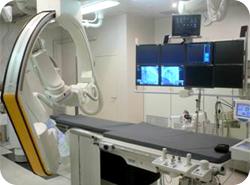 血管を造影する機器の写真。ベッドがあり血管を映し出す液晶がたくさんある。